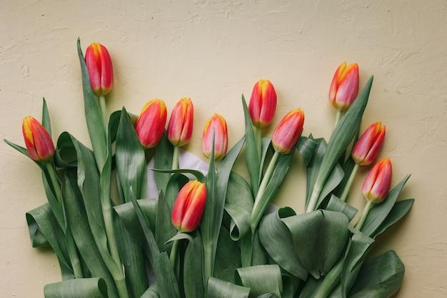 밝은 분홍색 배경에 아름다운 빨간 튤립 유럽 꽃집은 튤립 꽃다발을 준비합니다