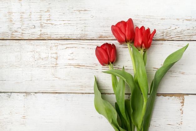 Красивые красные тюльпаны на белом деревянном столе