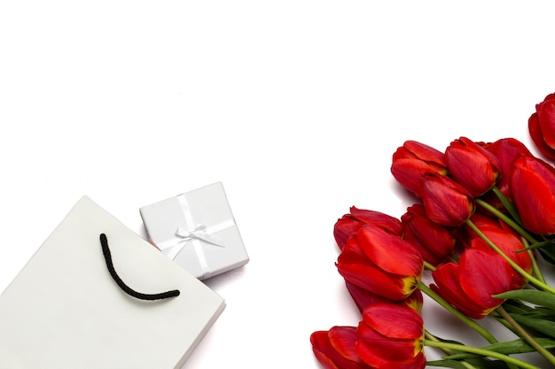 Красивые красные тюльпаны, упаковка и подарочная коробка на белом. вид сверху.