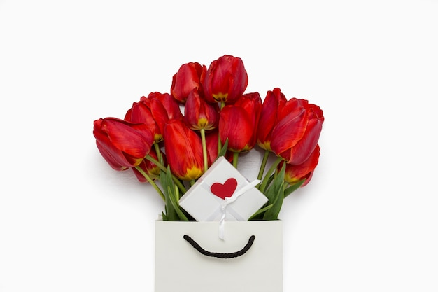 Beautiful red tulips in a paper gift bag, gift box with a heart on a white
