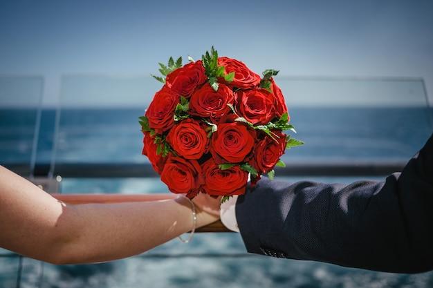 Красивый красный свадебный букет из красных роз, держась руками на фоне моря. брак