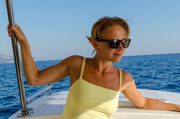 Красивая красная женщина наслаждается круизом на яхте в жаркий летний день