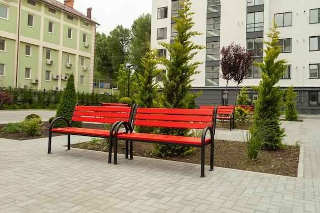 Красивая красная деревянная скамейка во дворе новостройки