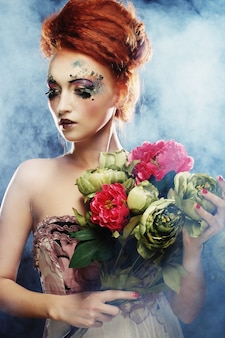 Beautiful redhair woman  holding flowers