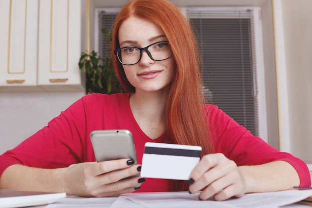 Beautiful redhaired female verifies credit card account balance on smart phone with mobile banking application, does shopping online. mobile payments. woman buys goods in internet enters security code