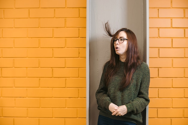 Beautiful redhaired girl wearing glasses and a green sweater is smiling against a yellow brick wall