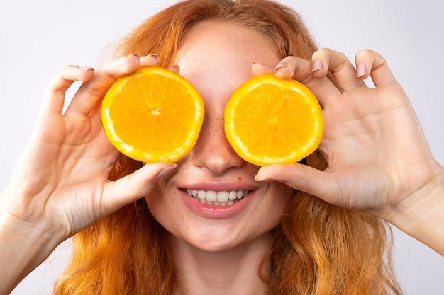 Красивая рыжеволосая радостная девушка с веснушками, красными кудрями и желтым макияжем. дольки апельсина и смех, эмоции. концепция красоты и спа.