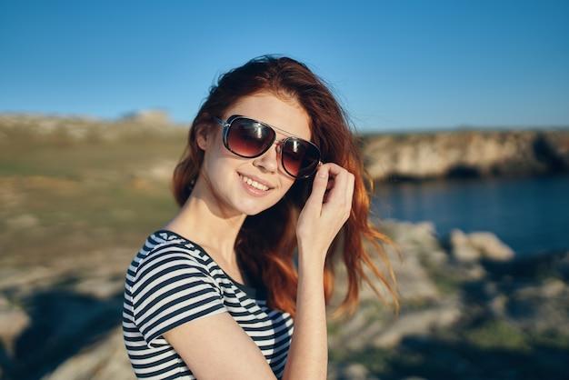 川の近くの山の自然にtシャツとサングラスで美しいredhaired女性