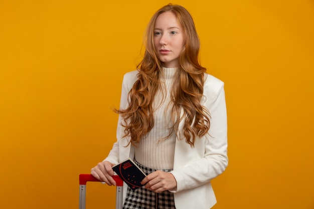 旅行で美しい赤毛の巻き髪の少女。次の旅行。ブラジルのパスポートを保持している女の子。黄色に。