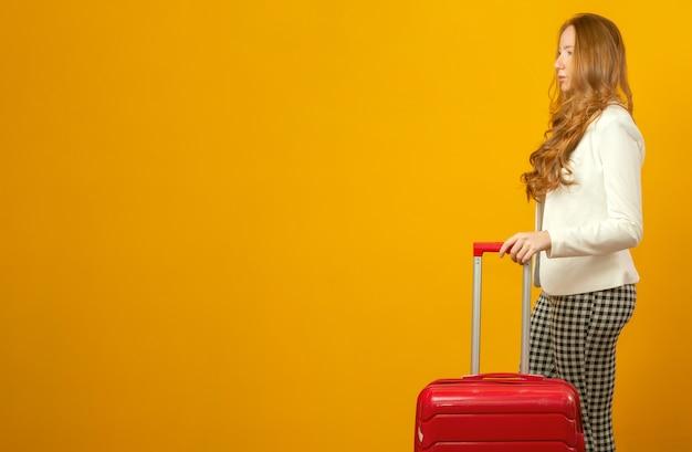 旅行で美しい赤毛の巻き髪の少女。次の旅行。スーツケース。黄色に。