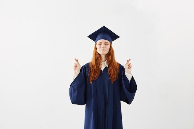 Beautiful redhead female graduate praying.