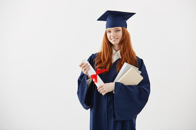 Beautiful redhead female graduate smiling holding books and diploma.