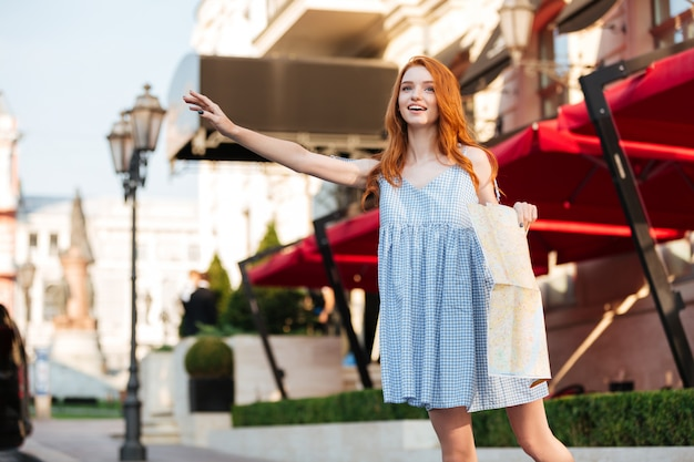 Beautiful redhead girl in dress holding a city guide map