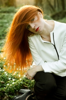 Beautiful redhead girl enjoys the sun