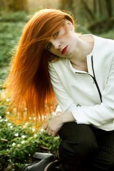 美しい赤毛の女の子は、太陽を楽しんでいます