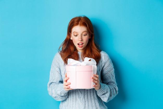 ピンクのかわいい箱に贈り物を持って、驚いた顔で現在を見て、青い背景の上に立っている美しい赤毛の女の子。