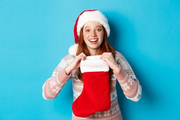 サンタの帽子をかぶった美しい赤毛の少女は、クリスマスの靴下を開き、驚いたように見え、クリスマスプレゼントを受け取り、青い背景の上に立っています。