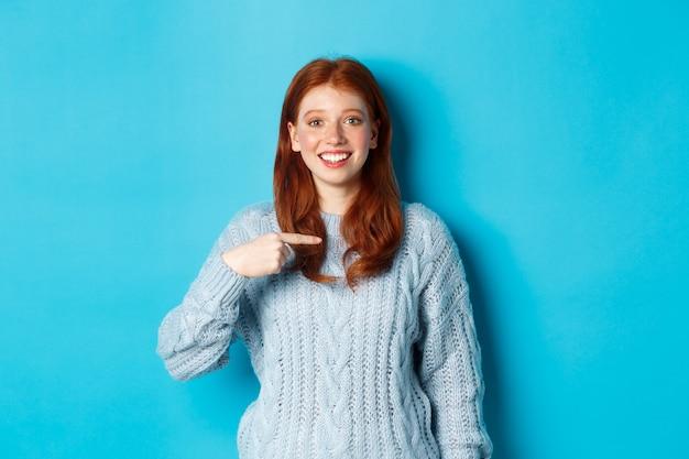 Bella ragazza rossa che indica se stessa e sorride felice, essendo scelta, in piedi in maglione su sfondo blu.