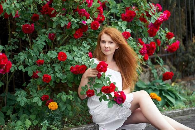 咲くバラの背景の上に座って、バラの枝を持って白いスタイリッシュなドレスを着て裸足で美しい赤毛の女の子。