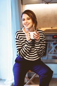 Красивая рыжая девушка с чашкой кофе ch, сидя на маленькой лестнице дома возле окна.