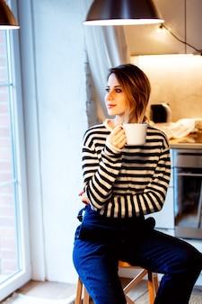 一杯のコーヒーと美しい赤毛の女の子は、窓の近くの自宅の小さな階段に座っています。