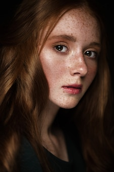 Beautiful redhead girl with a perfectly curls hair and classic make-up
