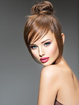 スタイルの髪型を持つ美しい赤毛の女の子。大きな青い目をしたセクシーな若い女性の肖像画。ファッションモデルのポーズ