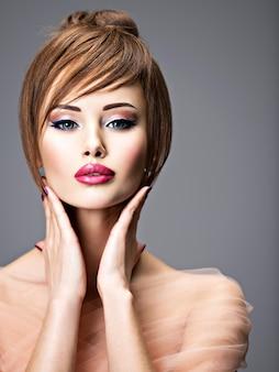 스타일 헤어 스타일으로 아름 다운 빨간 머리 소녀입니다. 큰 파란 눈을 가진 섹시 한 젊은 여자의 초상화. 패션 모델 포즈