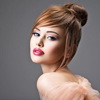 Красивая рыжая девушка с стильной прической. портрет сексуальной молодой женщины с большими голубыми глазами. позы модели