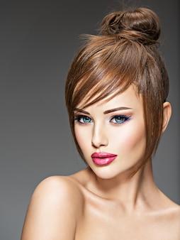 Bella ragazza rossa con acconciatura di stile. ritratto di una giovane donna sexy con grandi occhi azzurri. pose del modello di moda