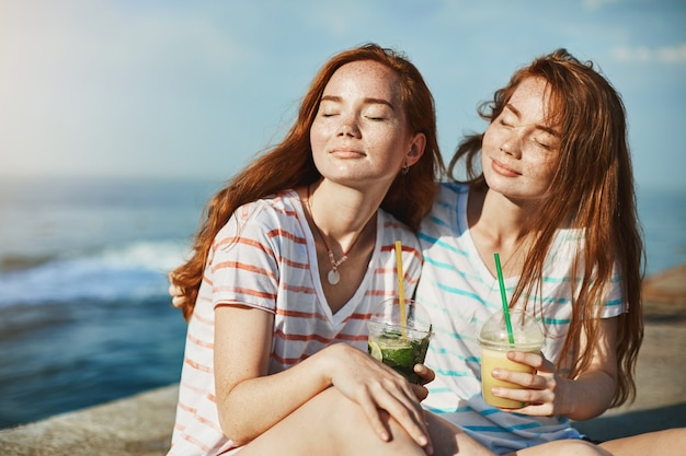 Beautiful redhead girls enjoying warm sunlight, closing eyes and resting near sea, drinking cocktails, hugging and closing eyes to relax