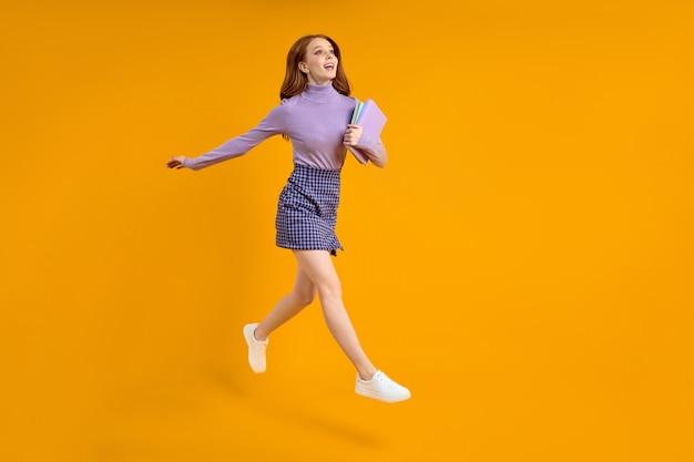 주말에 점프하는 아름다운 빨간 머리 아가씨는 캐주얼한 옷을 입고 집으로 가는 길에 노트북을 들고 있습니다.