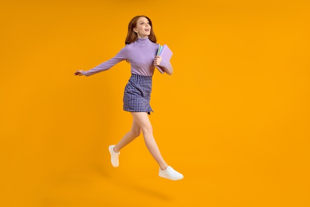 Beautiful redhead lady at weekend jumping hold notebooks in hands on way home in air wearing casual ...