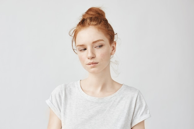Beautiful redhead model with freckles dreaming biting lip.