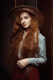 古い通路でポーズをとる麦わら帽子の長いウェーブのかかった髪の美しい赤毛モデル