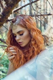 森の中の顔に大きな目とそばかすのある美しい赤毛のノルウェーの女の子。自然の中で赤毛の女性のクローズアップの肖像画、太陽の下で長い波状の赤い髪の素晴らしい神秘的な外観。ヘアケア