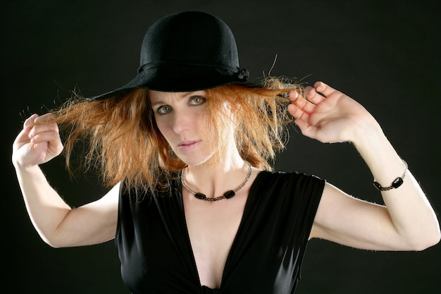 Beautiful redhead woman in black, hat and jewels