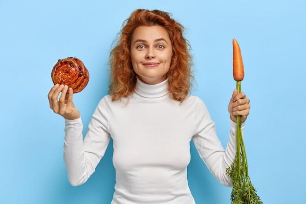 Красивая рыжая женщина выбирает между свежей морковью и сладкой булочкой