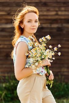 ダークブラウンの背景に風に吹かれた髪のデイジーの花束を保持している美しい赤毛の女性