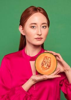 Bella donna della testarossa che tiene un melone