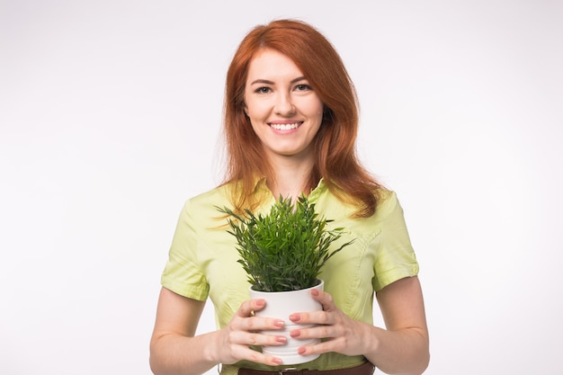 Beautiful redhead woman holding pot with a plant on white background