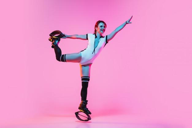 カングーでジャンプ赤いスポーツウェアで美しい赤毛の女性がピンクの壁に靴をジャンプします。