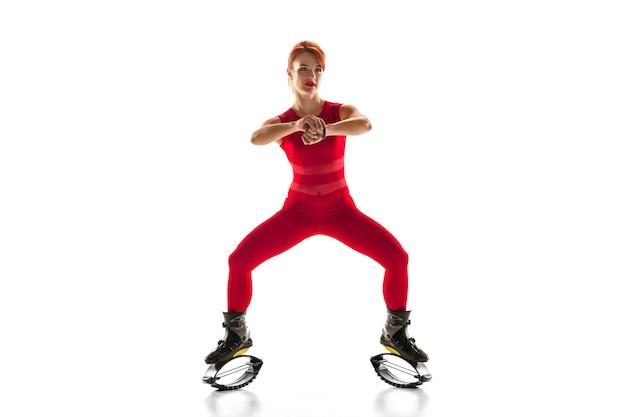 カングーでジャンプする赤いスポーツウェアの美しい赤毛の女性
