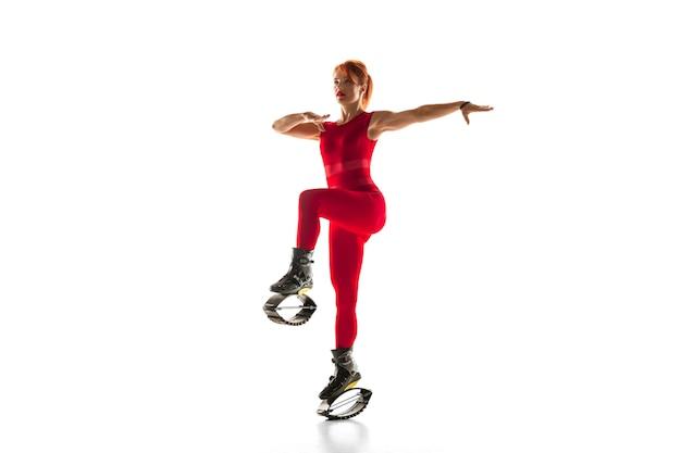 캥거루에서 점프하는 빨간 운동복을 입은 아름다운 빨간 머리 여자