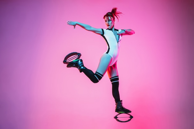 カンゴージャンプ靴でジャンプする白いスポーツウェアの美しい赤毛の女性