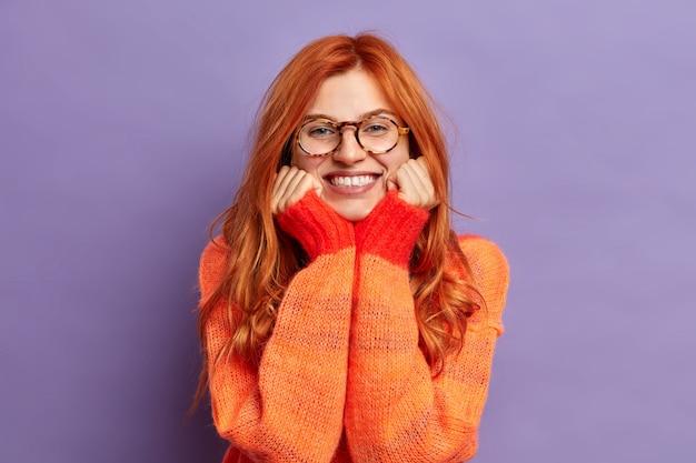 Bella donna rossa tiene le mani sotto il mento e sorride ammira ampiamente qualcosa vestito con un maglione caldo.