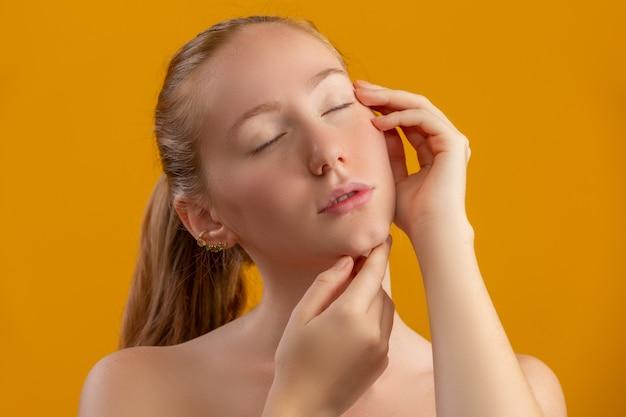 美しい赤毛の女性。保湿クリームまたはフェイスプライマー。若さとスキンケアのコンセプト。フェイシャルトリートメント。美容、美容、スキンケアのコンセプト。体液クリーム。