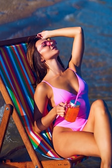 彼女の手でジュースのガラスと海の近くで日光浴をしている長椅子の美しい赤毛の女性