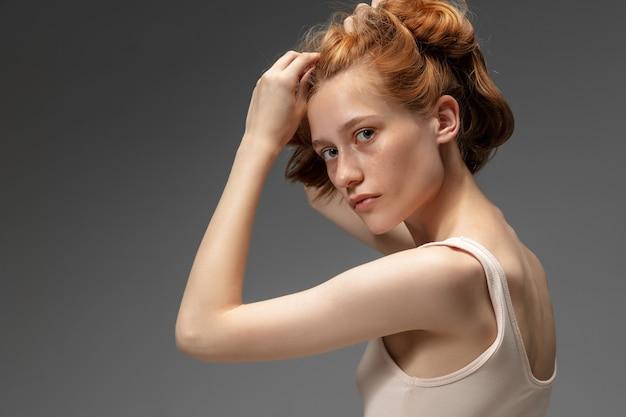 회색 스튜디오 벽에 아름다운 빨간 머리 여자, 패션