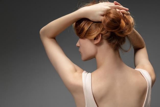 회색 벽에 아름 다운 빨간 머리 여자